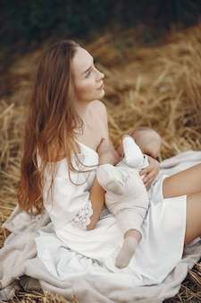 Mother with cute daughter. mom breastfeeding her little daughter. woman in a white dress.