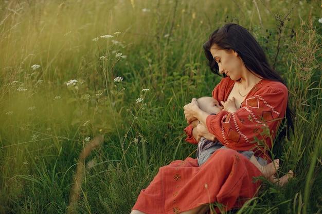 かわいい娘を持つ母。彼女の幼い息子を母乳で育てるママ。赤いドレスを着た女性。