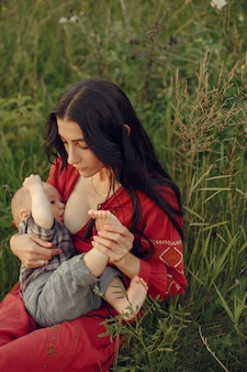 Mother with cute daughter. mom breastfeeding her little son. woman in a red dress. Free Photo