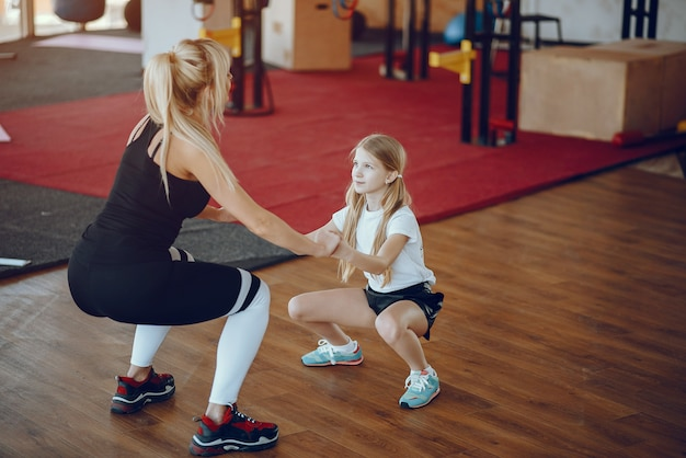 Mother with cute daughter play sports in the gym