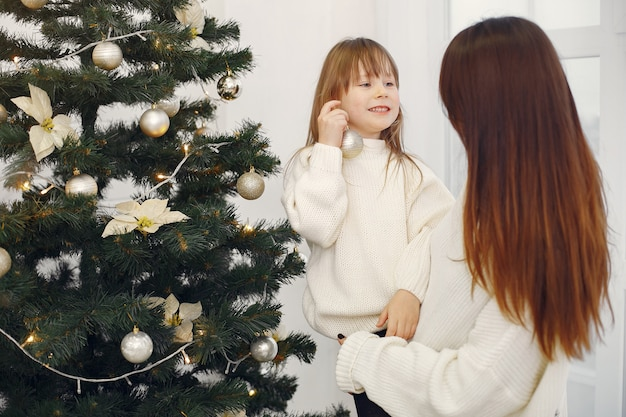 Mother with cute daughter standing near christmas tree