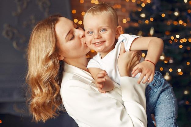 Мать с милым сыном дома возле елки
