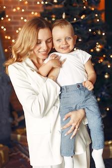 クリスマスツリーの近くに家でかわいい息子を持つ母