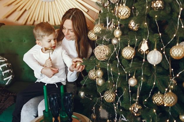 クリスマスツリーの近くのかわいい息子を持つ母