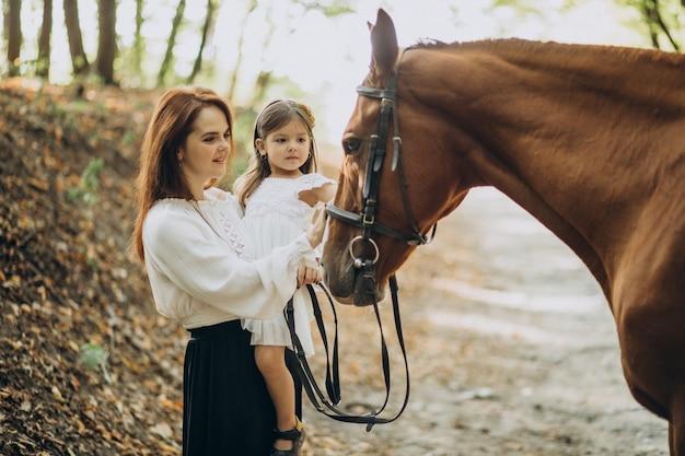 Мать с дочерью и лошадью в лесу