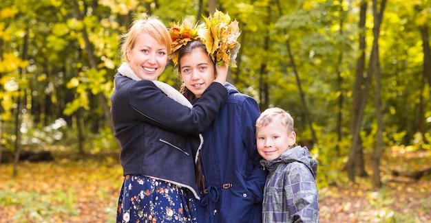 딸과 아들 화창한 단풍 공원에서 어머니.