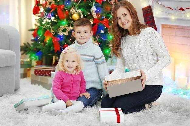 クリスマスツリーの近くに娘と息子を持つ母