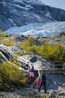 Mother with daughter are hiking at the mountains and the glacier nigardsbreen at the background