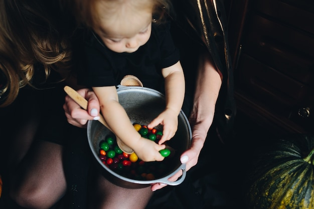 Mother with daughter in arms and is with hands between the candies