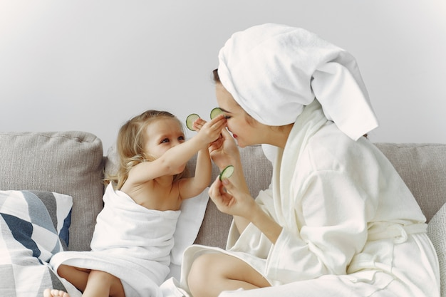Mother with daughter in bathrobe and towels