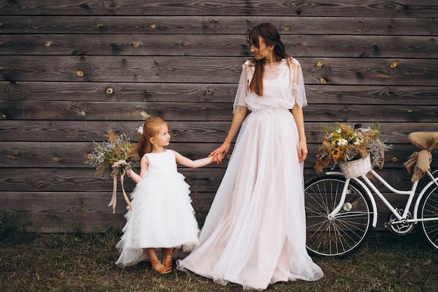 Mother with daughter in beautiful dresses by the bicycle