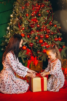 Мама с дочкой у елки распаковывают подарки
