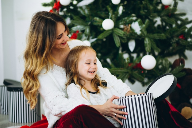 Mother with daughter by christmas tree