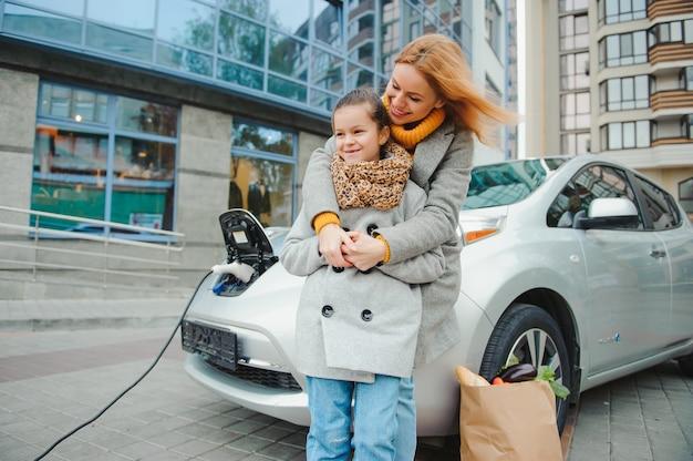 Мать с дочерью заряжает электромобиль на азс и разговаривает по мобильному телефону.