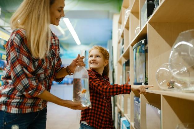 ペットショップで水族館を選ぶ娘を持つ母。ペットショップで道具を買う女性と幼い子供、家畜のアクセサリー