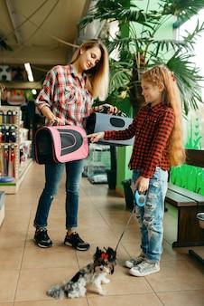 애완 동물 상점에서 가방을 선택하는 딸과 어머니