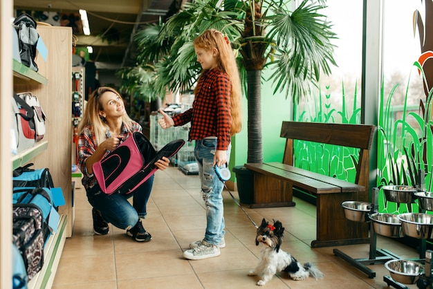 Mother with daughter choosing bag for little puppy in pet store. Premium Photo