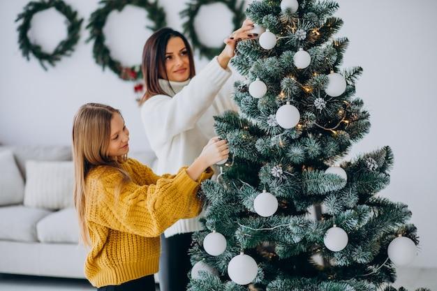 크리스마스 트리를 장식하는 딸과 어머니