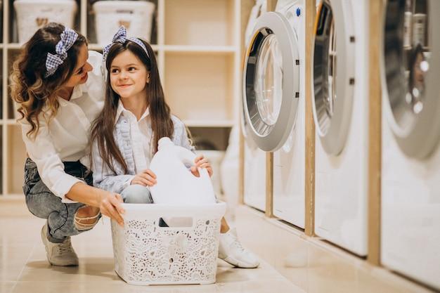 セルフサービスコインランドリーで洗濯をしている娘を持つ母