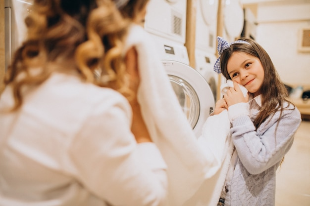 Mother with daughter doing laundry at self serviece laundrette