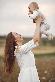 Madre con figlia. famiglia in un campo. ragazza appena nata. donna in abito bianco.