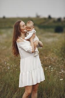 娘を持つ母。フィールドの家族。新生児の女の子。白いドレスを着た女性。