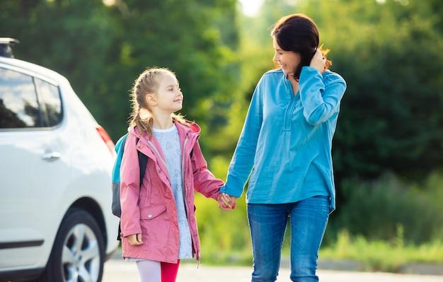 屋外の駐車場で手をつないで学校に戻る娘を持つ母