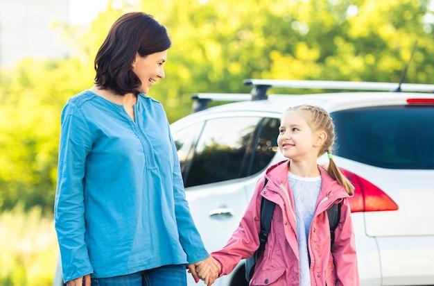 車で屋外で手をつないで学校に戻る娘を持つ母