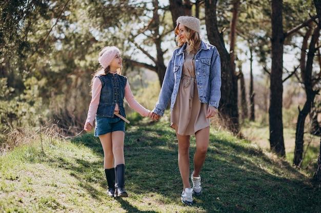 Мать с дочерью веселятся в лесу