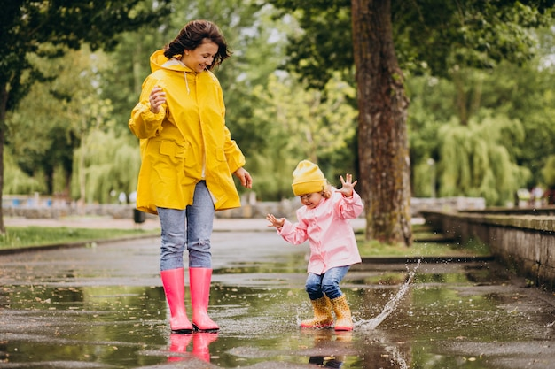 Mother with daughter having fun jumping in puddles
