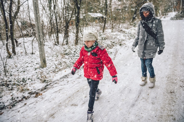 Mother with daughter hiking in snowy forest