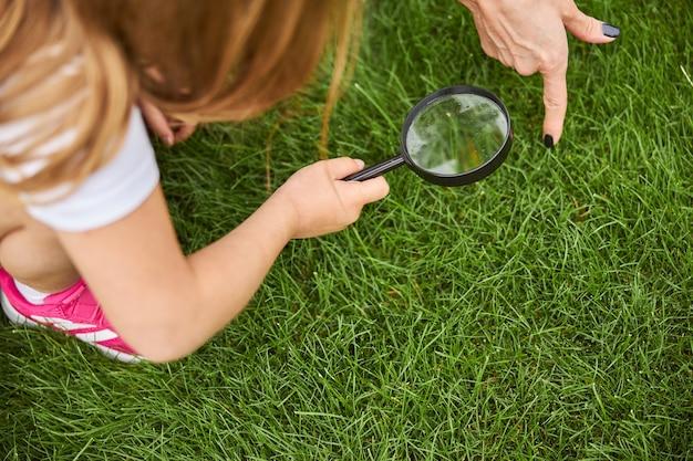 그것을 통해 자연을 보면서 딸이 렌즈를 손에 들고 어머니