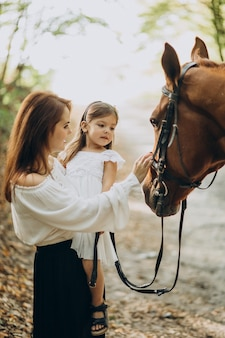 Mother with daughter and horse in forest