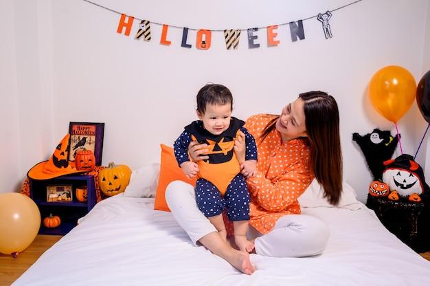 Мать с дочерью в костюме для празднования хэллоуина дома. малыш с мамой в оформлении спальни.