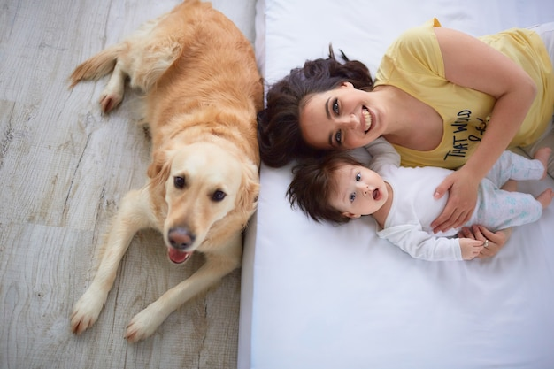 The mother with daughter lie on the bed and dog sitting near bed