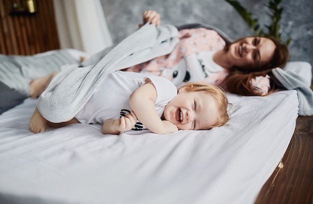The mother with daughter lie  on the bed