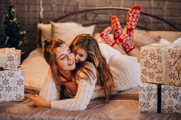 クリスマスのベッドで横になっている娘を持つ母