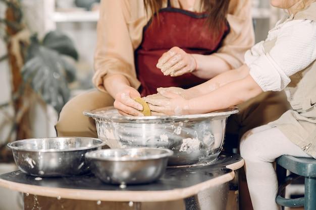 Мать с дочерью делает вазу в гончарной мастерской