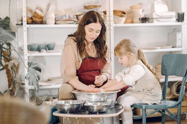 Mother with daughter makes vase in a potterystudio