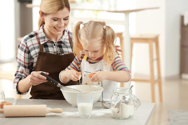 Мать с дочерью вместе делают тесто на кухне