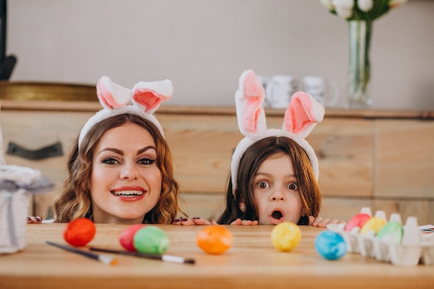 Mother with daughter painting eggs for easter