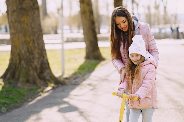 Mother with daughter in a park with skate