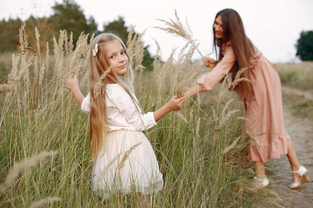 Mother with daughter playing in a autumn field