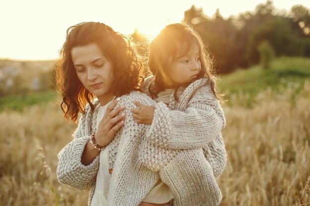Мать с дочерью, играя в летнем поле