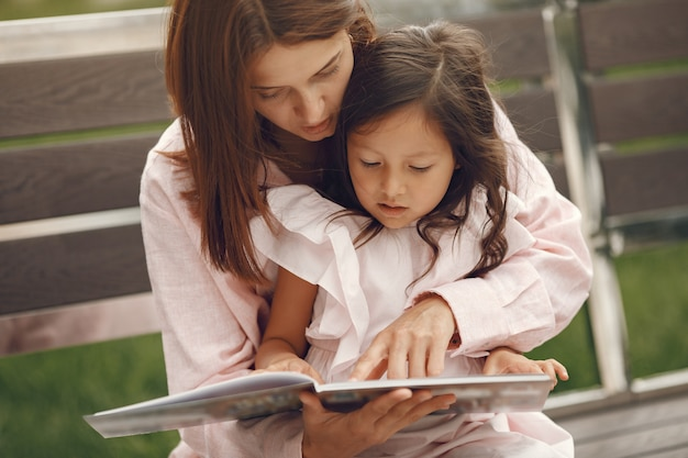 Mother with daughter reading a book in the city