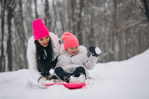 Мать с дочерью катается на тарелке в зимнем парке