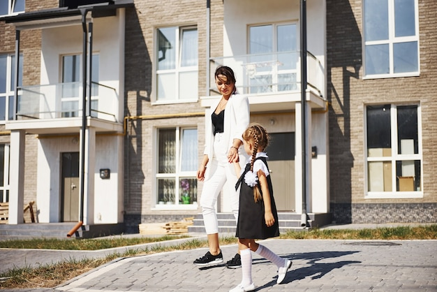 Mother with daughter in school uniform outdoors near building.