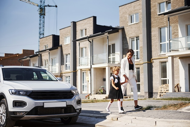 Mother with daughter in school uniform outdoors near white car.