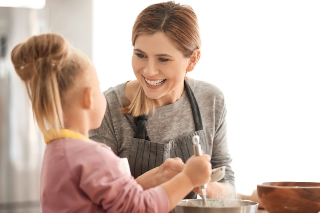 Mother with daughter sifting flour into bowl in kitchen