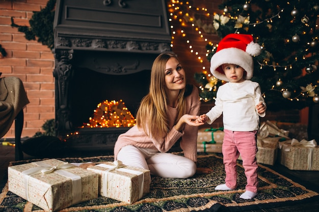 Mother with daughter sitting by christmas tree